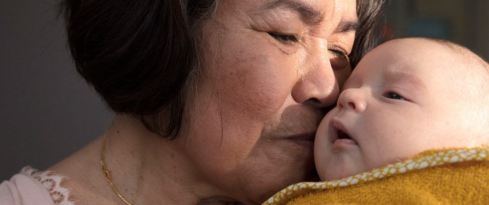 Grandmother kissing baby