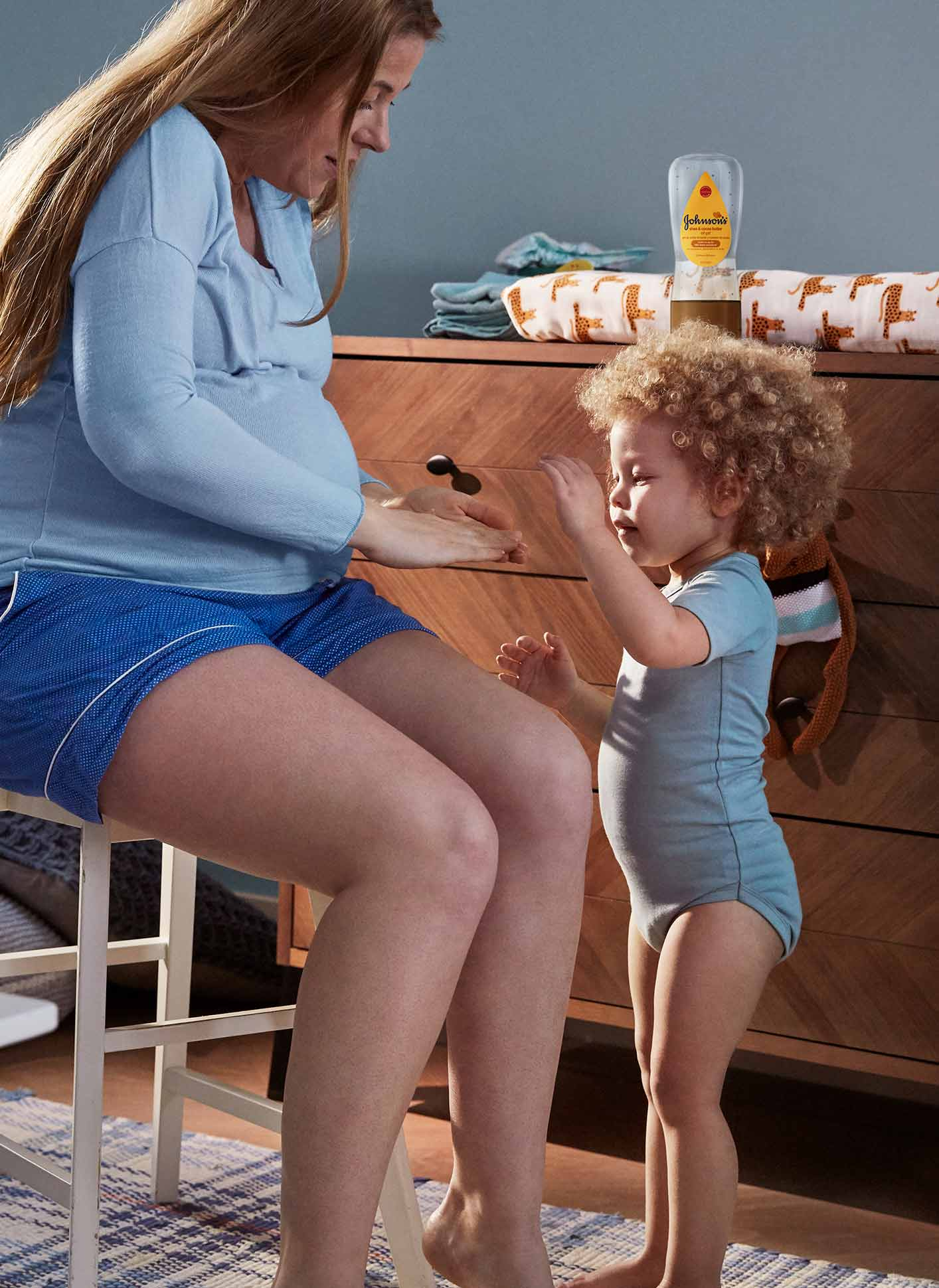 woman applying baby oil into legs